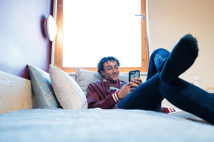 Student on his phone in a bedroom