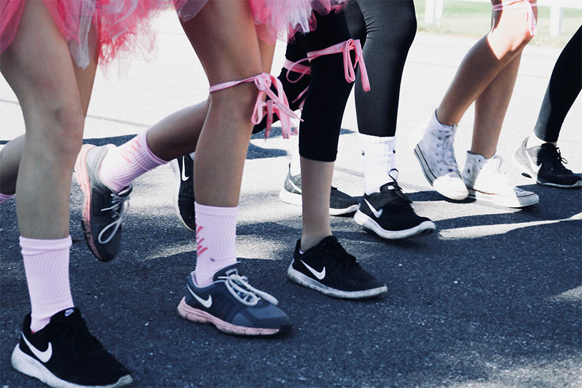 A collection of people's legs earing trainers and pink ribbons tied around their legs