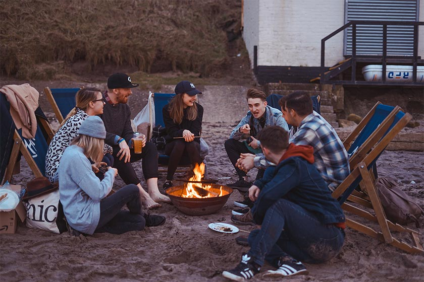A group of young adults sat in deck chairs around a campfire on a beach