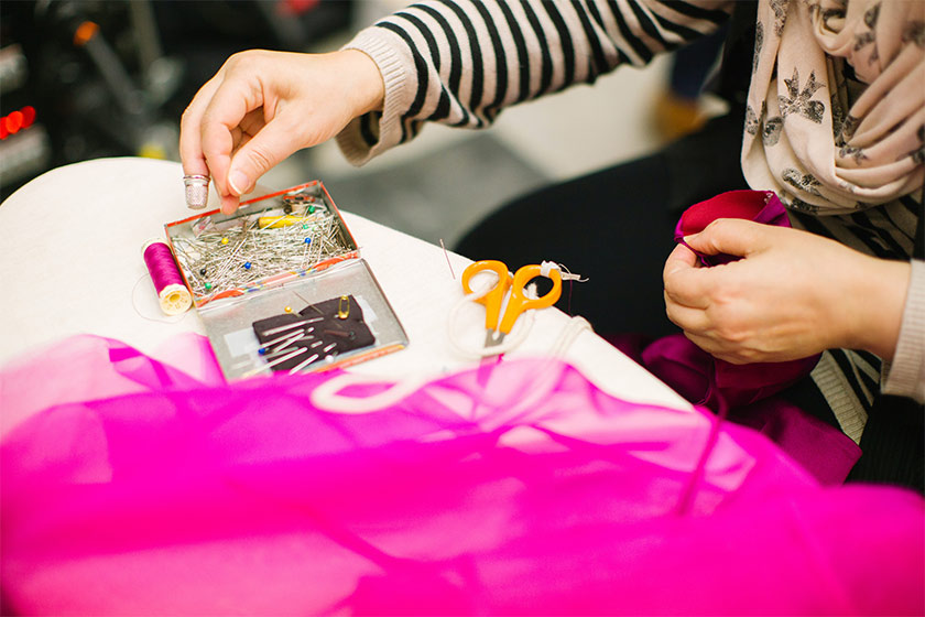 A woman gettign something out of her sewing kit whilst she sews using a pink fabric