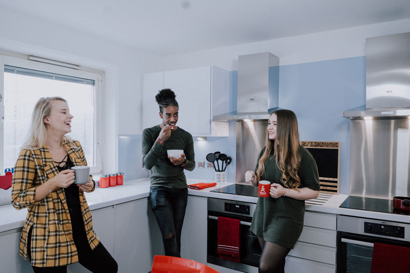 A group of students chatting in a kitchen at Manna Ash House.