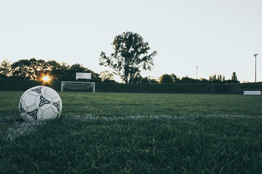 A football in a field, in-front of a goal