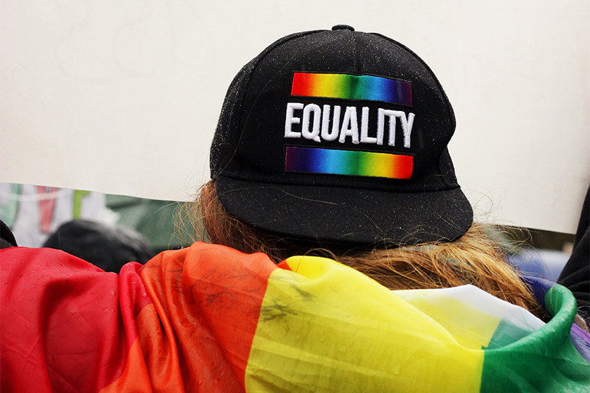 """Rear view of somebody holding a placard whilst wearing a flag and a hat with the pride colours and the word """"Equality"""""""