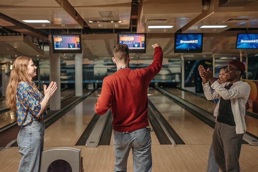 Three people enjoy a game of ten-pin bowling