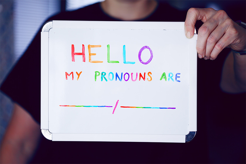 """A person in a black t-shirt holding a whiteboard with the writing """"Hello my pronouns are"""" in rainbow colours"""