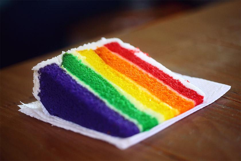A slice of rainbow cake on a white napkin