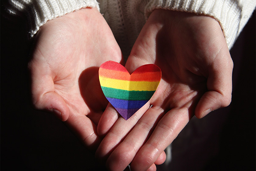 Two hands cupping a paper heart coloured in the colours of the rainbow