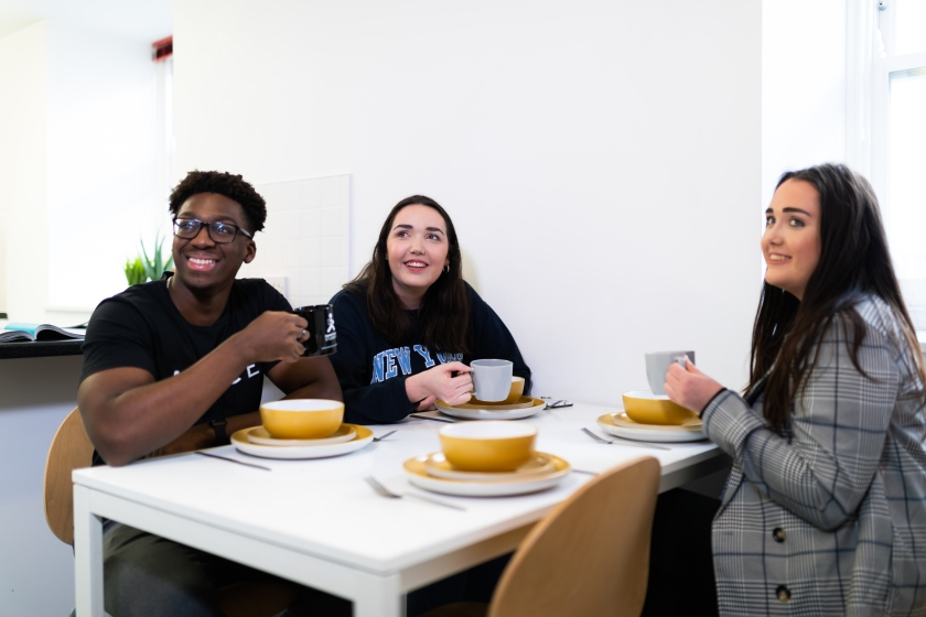 Students sitting at a dinner table eating, talking and laughing