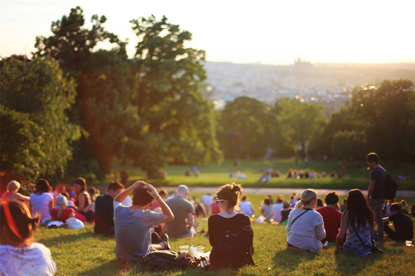 People gathered on a hill in the park looking at the sunset in the background