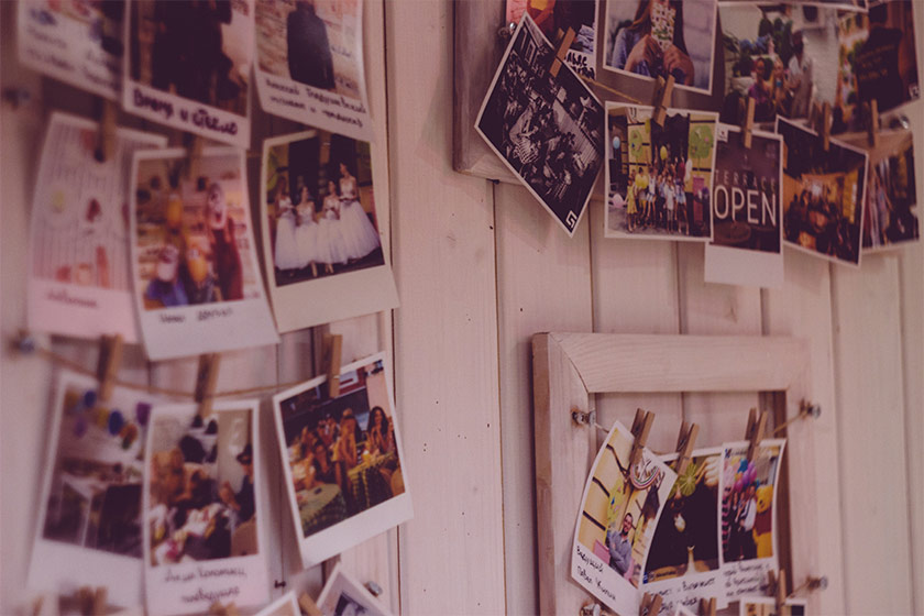 A collection of polaroid photographs with captions written on pinned to a noticeboard