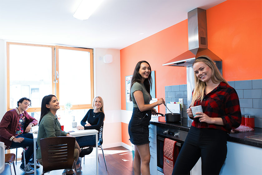 Students hanging out and cooking in the kitchen