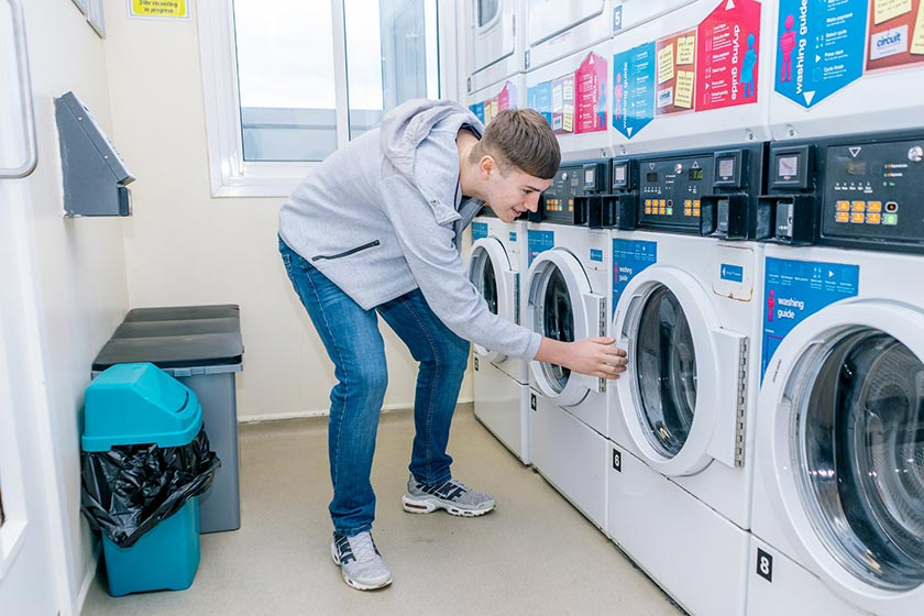 A student loads washing in the laundry facility.