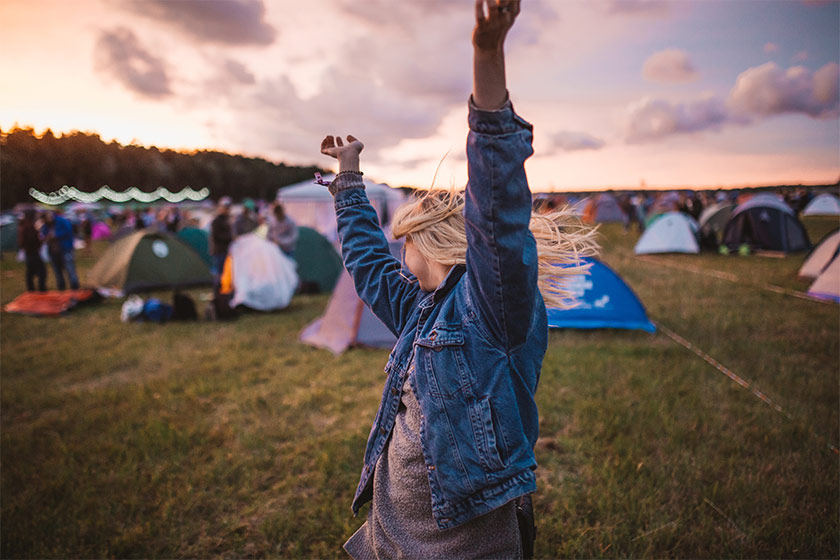 A young blonde girl dancing at a festival with tents in the background