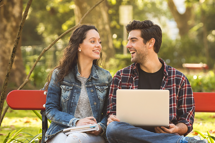 A young couple chat while sitting on a bench in a park