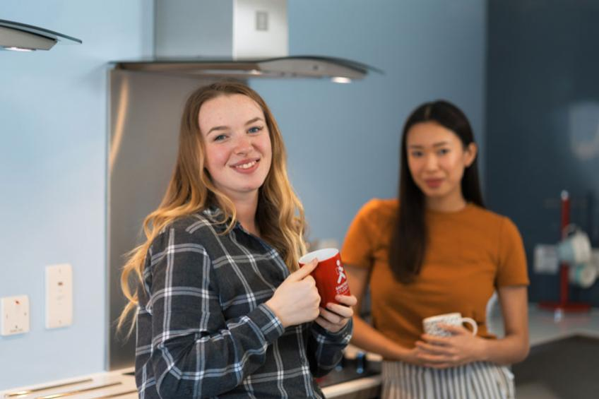 Students in a kitchen having a hot drink together.