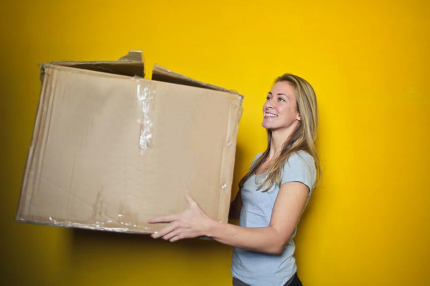 A young woman picks up a large cardboard box.