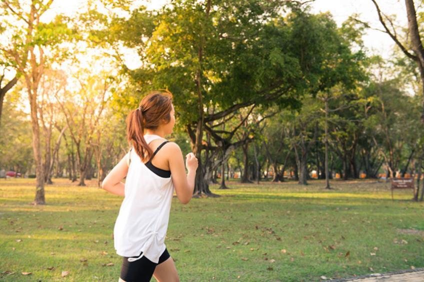 Woman running through a green park