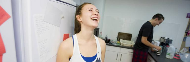 A student stood laughing in their shared kitchen.