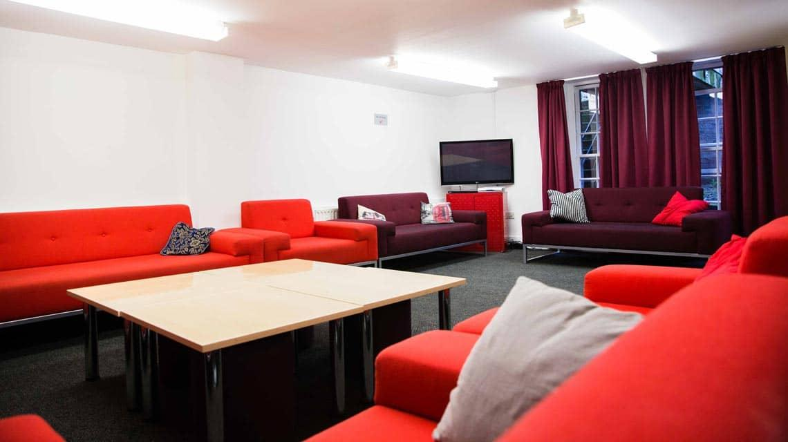 The common room at Alliance House showing sofas and a TV.