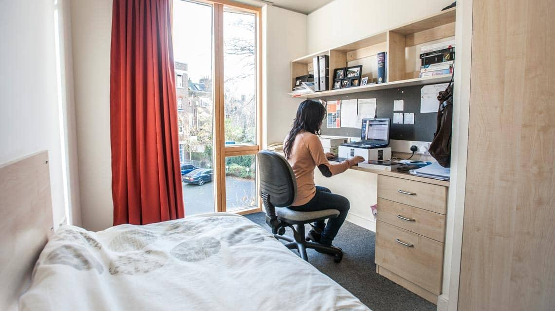 A student sat at a desk in her Alliance House bedroom