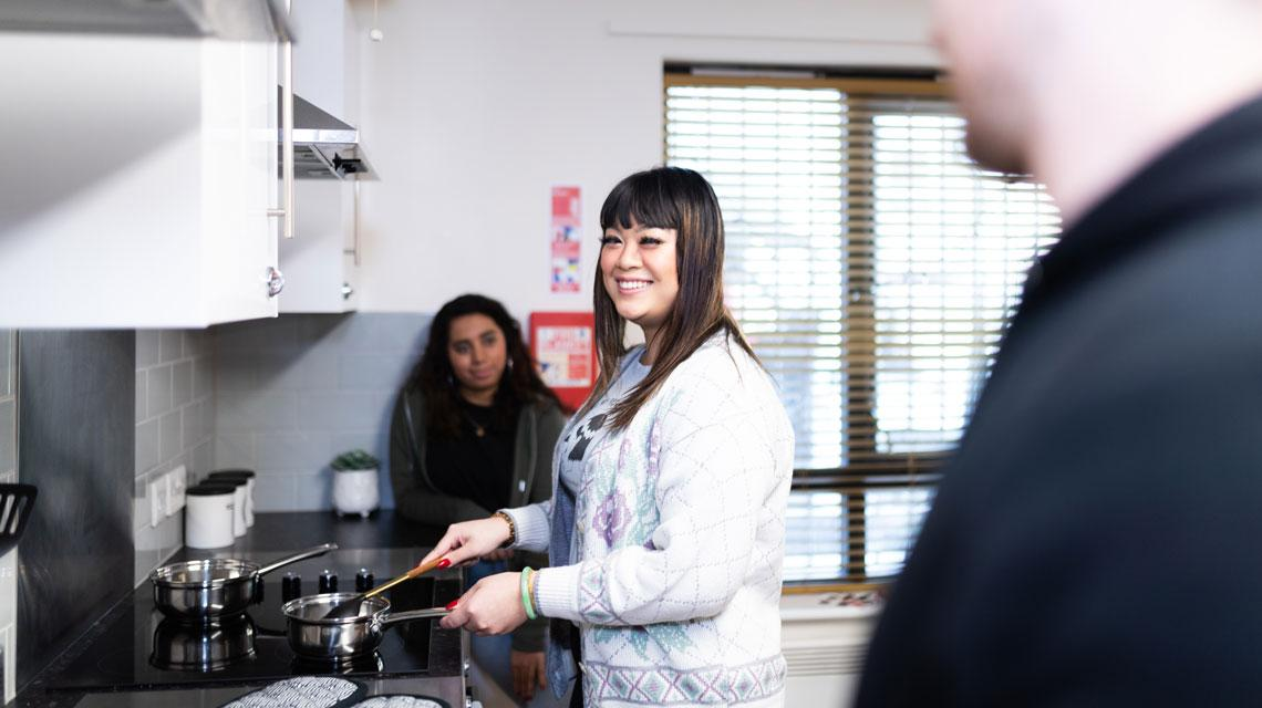 Students smiling and cooking in their shared kitchen