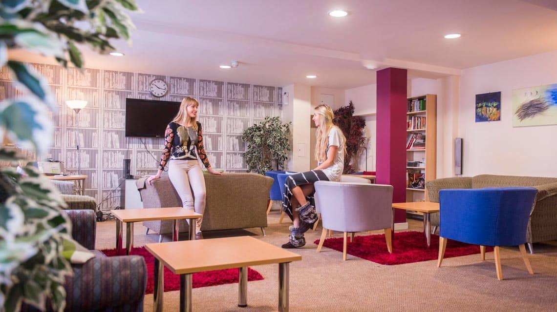 Two students talking in the Don Gratton House shared common room