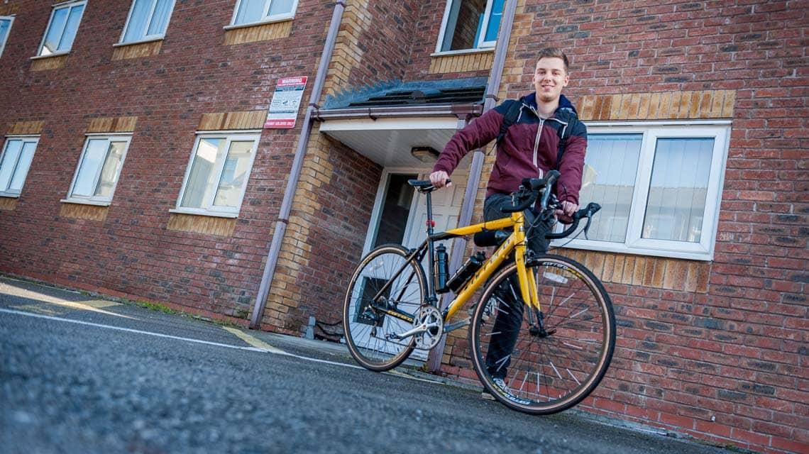 A male student stood outside Grange Court and the Ridings with his bike