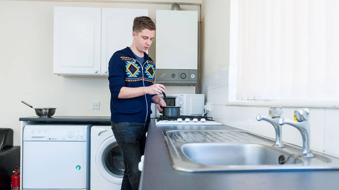 a male student cooking in his Grange Court kitchen