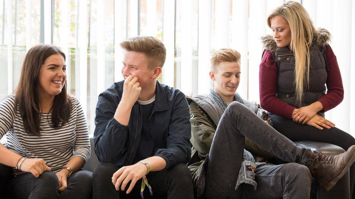 Four friends laughing in the common room