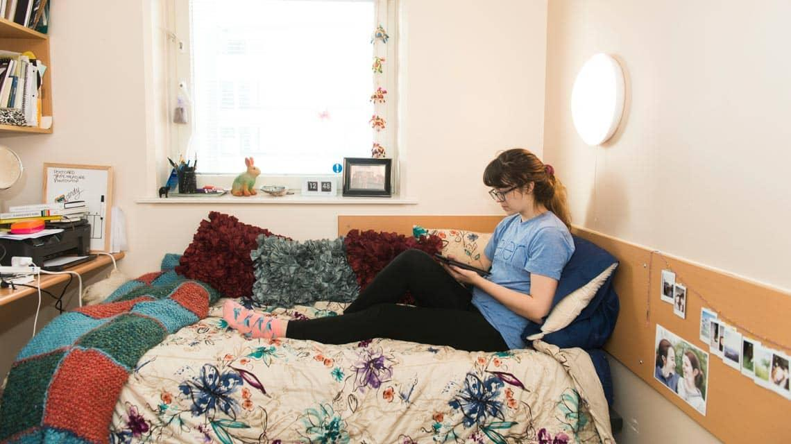 A student sat on their bed in Manna Ash House