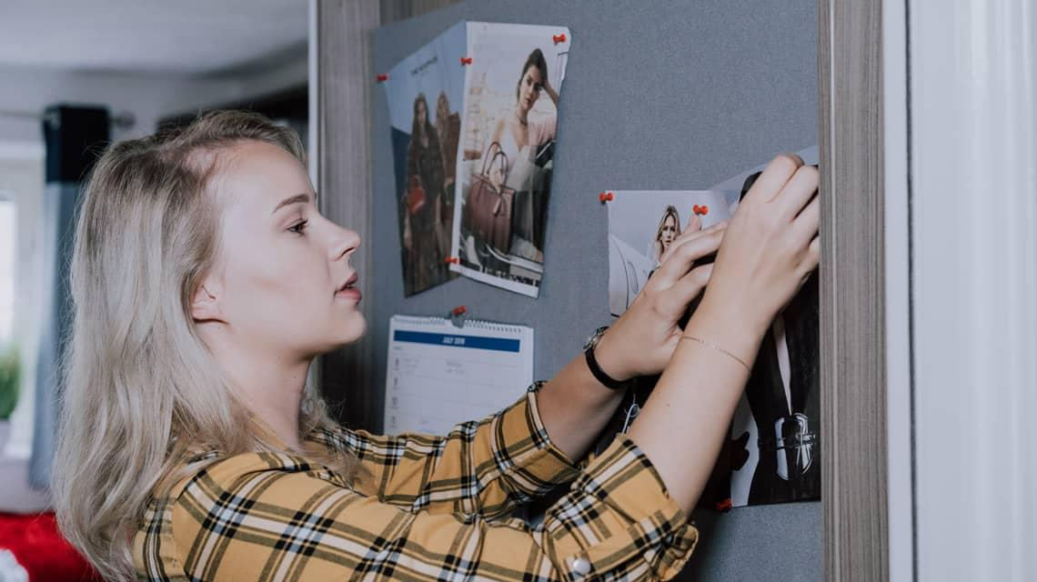 A student pinning something to her pinboard.