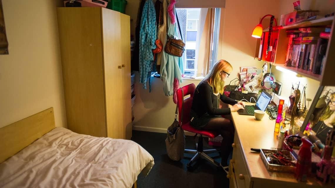 A student studying at her bedroom desk