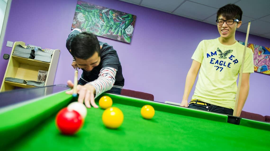 Two students playing pool at Oak and Willows House