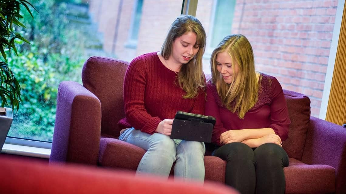 Two female students watching something on a tablet device