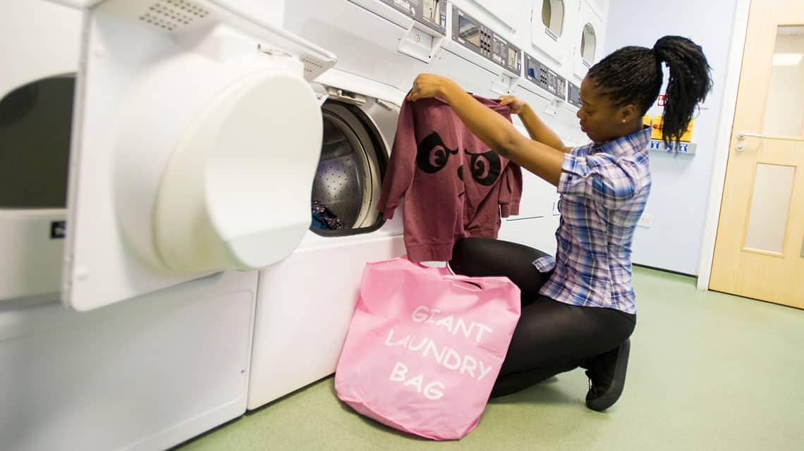 A student doing her laundry at Oak and Willows House