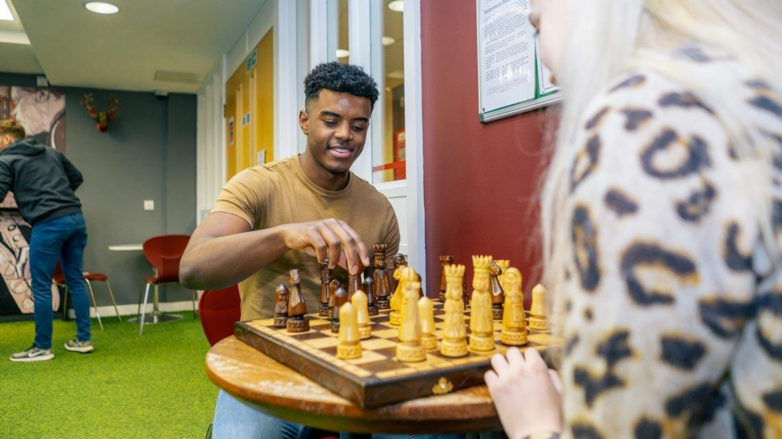 Two students playing chess in the common room at Wardley House