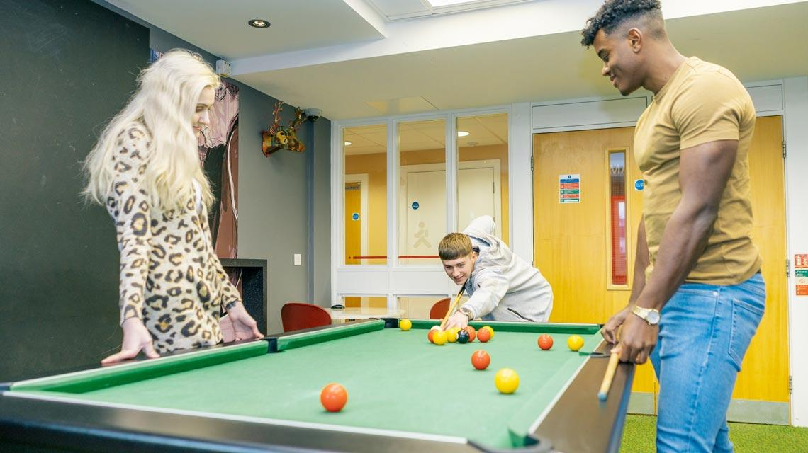 Students playing pool in the common room at Wardley House