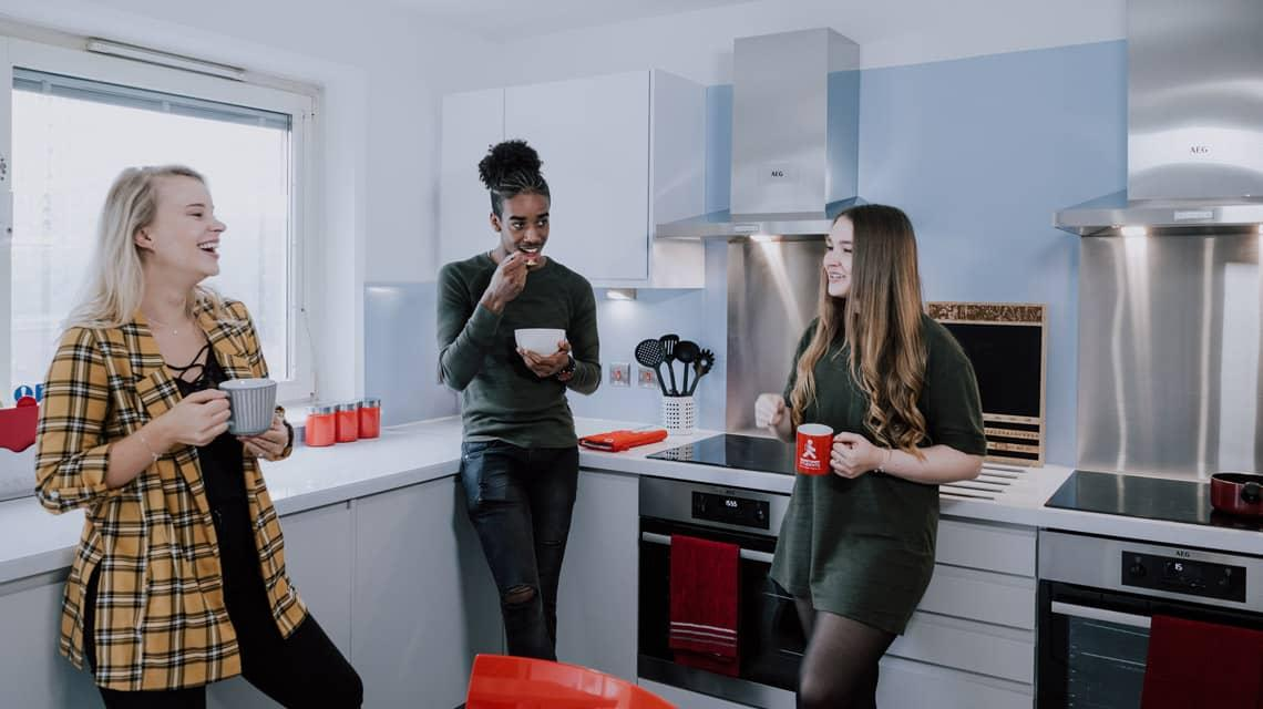 Students eating and talking in their shared kitchen