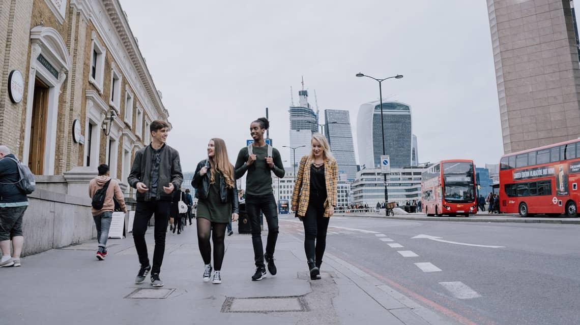 Four students walking through London