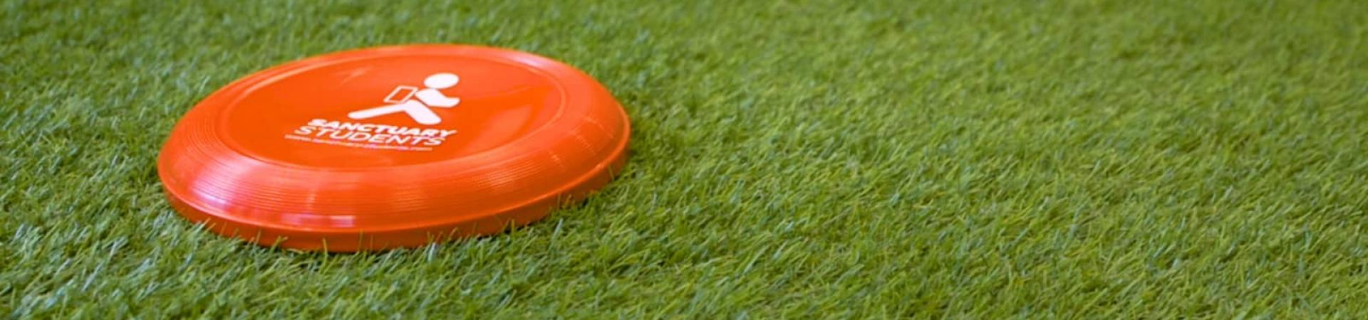A red Sanctuary Students frisbee lying on grass