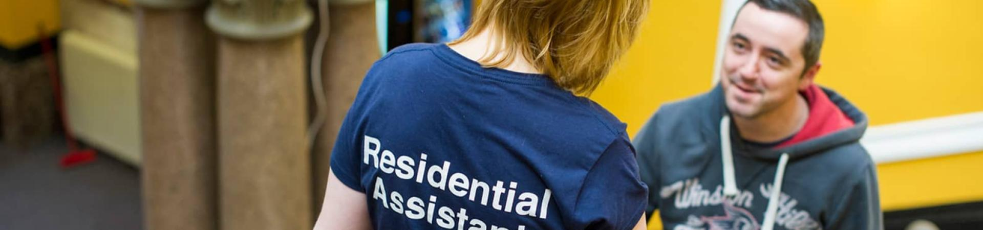 A residential assistant speaks with a student in the communal area.