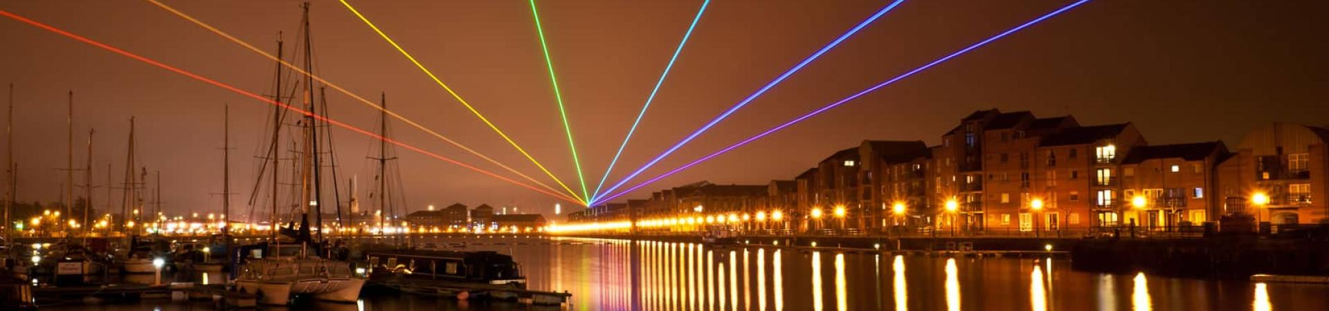 A waterside cityscape of Preston with lights in the background