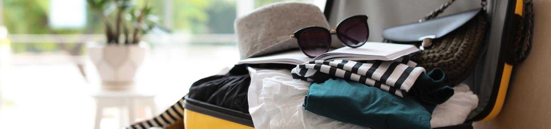 An open yellow suitcase with clothes, a hat and sunglasses inside